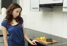 Молодая женщина смотря нездоровую еду стоковое фото rf