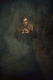 Молодая женщина смотря сразу на камере, стоя в тумане  Стоковое фото RF