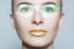 Молодая женщина смотря с футуристическими умными стеклами Стоковые Фото
