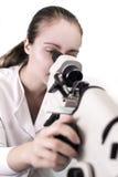 Молодая женщина смотря через микроскоп Стоковые Изображения