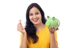 Молодая женщина сохраняет деньги в копилке стоковая фотография rf
