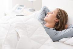 Молодая женщина спать в спальне стоковое изображение rf