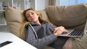 Молодая женщина спать с компьтер-книжкой на софе дома видеоматериал