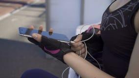 Молодая женщина спортсмена вводит наушники к телефону сток-видео