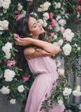 Молодая женщина среди роз в саде стоковое фото rf