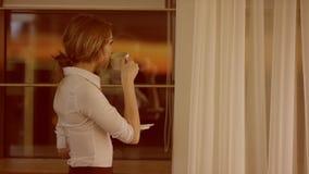 Молодая женщина стоит перед окном и выпивает чашку чаю или кофе акции видеоматериалы