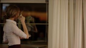 Молодая женщина стоит перед окном и выпивает чашку чаю или кофе видеоматериал