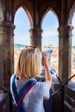 Молодая женщина стоит na górze башни с часами и смотрит старый городок в Праге используя телескоп Стоковая Фотография