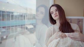Молодая женщина стоящ и смотрящ вне окно акции видеоматериалы