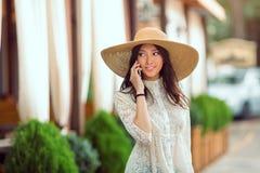 Молодая женщина стоя близко кафе и беседа телефоном Стоковое Изображение RF