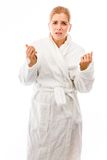 Молодая женщина стоя в купальном халате и смотря потревоженный стоковое фото rf