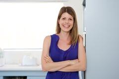 Молодая женщина стоя в кухне с ее пересеченными оружиями и усмехаться Стоковое Изображение