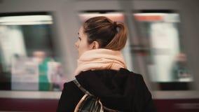 Молодая женщина стоя в платформе метро на фоне проходить поезд Метро девушки ждать, который нужно пойти к работе Стоковая Фотография RF