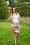 Молодая женщина стоя в траве стоковые фотографии rf