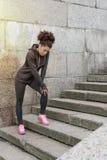 Молодая женщина стоя на лестницах Стоковые Изображения RF