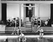Молодая женщина стоя на доске подныривания окруженной играть группы людей (все показанные люди нет более длинные живущих и нет стоковое фото
