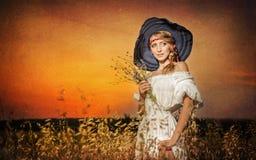 Молодая женщина стоя на пшеничном поле с восходом солнца на предпосылке Стоковые Изображения
