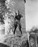 Молодая женщина стоя на стоге сена и держа вилу (все показанные люди более длинные живущие и никакое имущество не существует supp Стоковое Изображение RF
