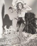 Молодая женщина стоя на стоге сена перед тенью кота на стене Стоковая Фотография