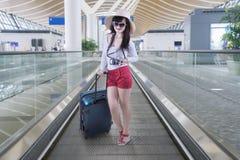 Молодая женщина стоя на эскалаторе Стоковые Изображения