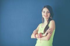 Молодая женщина стоя около темной стены с пересеченной рукой Стоковое Изображение