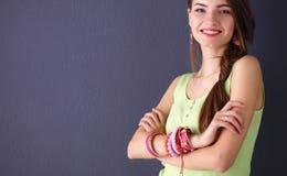 Молодая женщина стоя около темной стены с пересеченной рукой Стоковые Фотографии RF