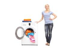 Молодая женщина стоя рядом с стиральной машиной стоковые фотографии rf