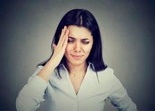 Молодая женщина страдая от головной боли касаясь ее голове с рукой Стоковое Изображение