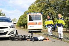 Молодая женщина с аварией велосипеда и приходя докторами медсотрудников стоковые изображения rf