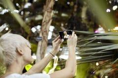 Молодая женщина с белокурыми короткими волосами делает selfie Принимать фото используя камеру телефона в зеленом парке Сфокусиров стоковые изображения