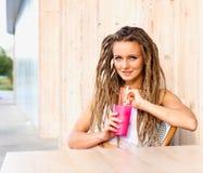 Молодая женщина с боязнями выпивая сидеть напитка внешний в городском кафе Образ жизни города кафа Вскользь портрет девушки подро Стоковое Изображение