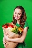 Молодая женщина с бумажной сумкой овощей Стоковая Фотография RF