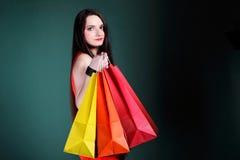 Молодая женщина с бумажной multi покрашенной хозяйственной сумкой Стоковая Фотография
