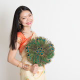 Молодая женщина с вентилятором пера павлина в индийском платье сари Стоковое фото RF