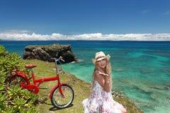 Молодая женщина с велосипедом на пляже стоковые изображения