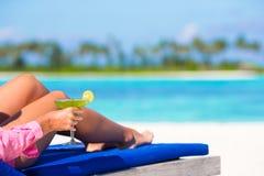 Молодая женщина с вкусным коктеилем на loungers пляжа Стоковое Изображение