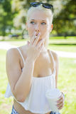 Молодая женщина с вопросами дыма в парке Стоковые Фотографии RF