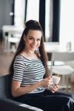 Молодая женщина с выпивая чаем в кафе Красивая взрослая женщина с чашкой капучино на кафе Усмехаясь брюнет с Стоковые Изображения RF