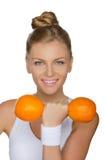 Молодая женщина с гантелями 2 зрелых апельсина Стоковое Изображение RF