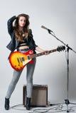 Молодая женщина с гитарой в ее руке Стоковое Изображение