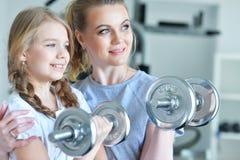 Молодая женщина с ее дочь-подростком в спортзале с гантелями Стоковые Изображения