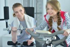 Молодая женщина с ее дочь-подростком в спортзале с гантелями Стоковое Фото