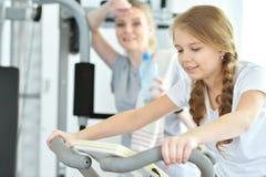 Молодая женщина с ее дочь-подростком в спортзале Стоковое фото RF