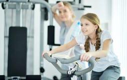 Молодая женщина с ее дочь-подростком в спортзале Стоковые Изображения