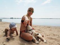 Молодая женщина с ее сыном и щенком на пляже Стоковые Фотографии RF