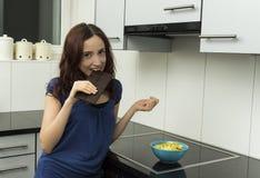 Молодая женщина сдерживая блок темного шоколада стоковое фото rf