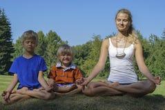 Молодая женщина с детьми размышляет в зеленом парке Стоковое Фото