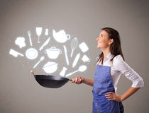 Молодая женщина с значками аксессуаров кухни Стоковое фото RF