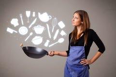 Молодая женщина с значками аксессуаров кухни Стоковые Изображения