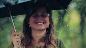 Молодая женщина с зонтиком в ее руках довольна с дождем и протягивает вне ее руки к падениям видеоматериал